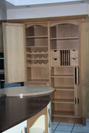 Tall cabinets fitted with spice drawers, wine racks, letter slots, chopping board and trays.