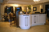 Modern painted kitchen, the curved island has many features the round end shown houses a carousel This furniture was a special commission.