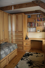 Compact bedroom in Art Décor style, Maple with Walnut detailing.With storage space at a premium this bedroom has been designed to maximise space, the bed (on castors)can stow away under the wardrobes, and has four deep storage drawers.