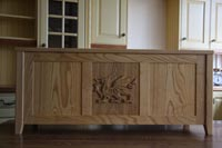 Ottoman made in solid Ash, this has a feature centre panel with carved Welsh Dragon, and the end